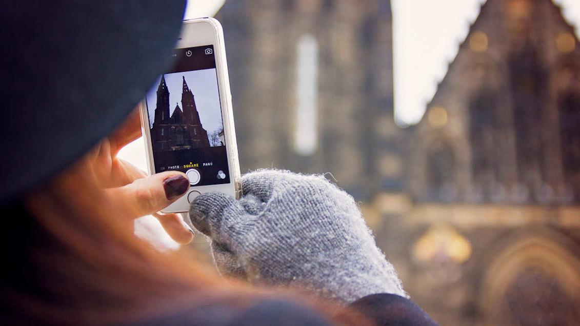 chica sacando una foto de una iglesia con el móvil
